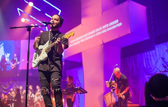 Stylish, excited, and youthful musician playing guitar and singing during an engaging worship service with amazing lighting.