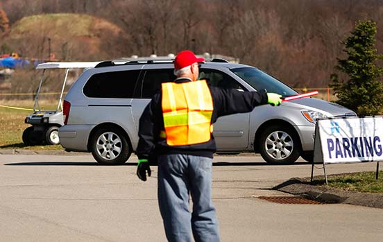 Warm, friendly, inviting older gentleman directing traffic and welcoming visitors as they enter the church parking lot.